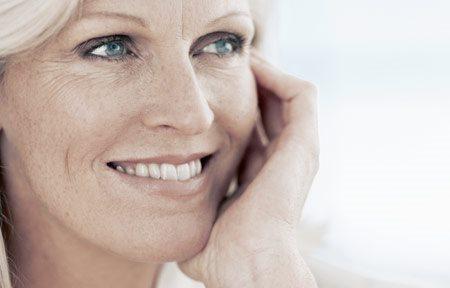 Hình ảnh người phụ nữ tuổi trung niên đang dùng tay sờ mặt của cô ấy