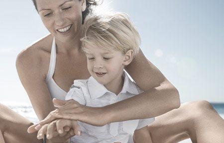 Hình ảnh người mẹ đang bôi kem chống nắng cho con trai