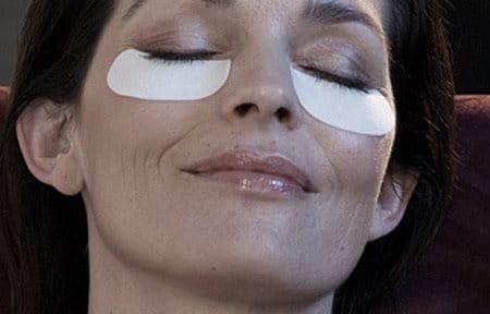Gương mặt người phụ nư với các miếng lót chăm sóc da dưới mắt của cô ấy
