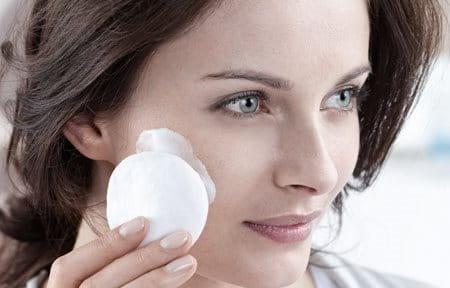 Hình ảnh cô gái dùng bông tẩy trang làm sạch gương mặt