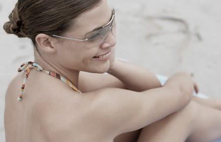 hình ảnh cô gái ngồi trên bãi cát trong bộ bikni