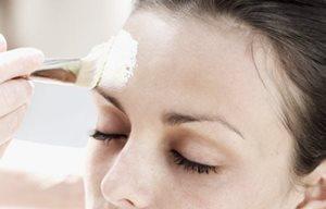 Người phụ nữ đang tiến hành tẩy da mặt với bàn chải